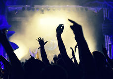 Crowd at a music concert, audience raising hands up Stock Photography