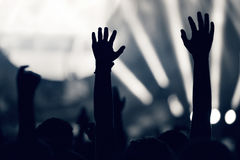 Crowd at a music concert, audience raising hands up, toned Royalty Free Stock Photo