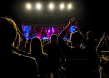 Crowd at music concert, people silhouettes backlit by stage lights. royalty free stock images