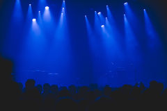 Crowd at music concert waiting for band to come on stage. Stock Images