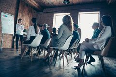 Crowd of nice stylish specialists sharks sitting on chairs listening classes courses coacher speaker growth strategy. Salary profit plan investments at stock photos