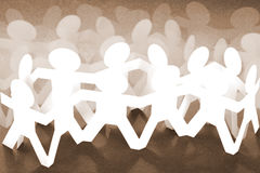 Crowd of Paper Chain People. On Brown Background Stock Photography
