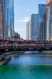 Crowd of party-goers cerlebrate on the bridge over a dyed-green Chicago River stock photo
