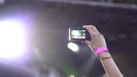 Crowd partying at open air rock concert. Young woman standing in the crowd holding smartphone in hands shooting video