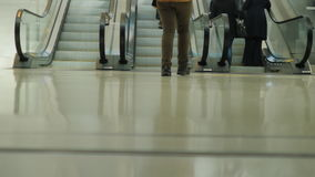 The crowd of passengers with luggage and shopping bags on wheels in a hurry to the escalator. In the picture can be seen. Passengers use the escalator at the stock video footage