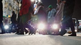 Crowd of pedestrians crossing busy city street at night, slow motion. Crowd of pedestrians crossing busy city street at night. Feet of people walking on stock footage