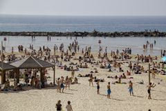 Crowd of people on the beach of Tel Aviv in hot day Stock Images