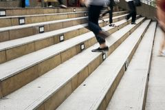 Crowd of people in blurred motion walking up and down the stair Royalty Free Stock Photos