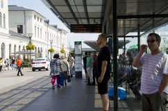 Crowd of people at a bus stop. A crowd of people at a bus stop in Sweden. Green bus at a stop in the background royalty free stock images