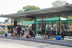 Crowd of people at a bus stop. A crowd of people at a bus stop in Sweden. Green and yellow buses at the stop royalty free stock photography