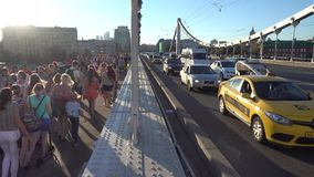 Crowd of people and cars move along the bridge stock video footage