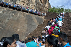 A crowd of people climb the ancient staircase up Sigiriya Rock in central Sri Lanka. Stock Images