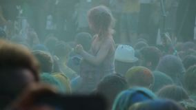 Crowd of people covered in colored paint hanging out at Holi color festival. Stock footage stock video footage