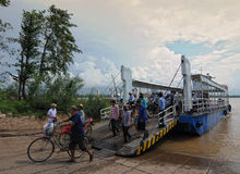 Crowd of people cross the river by ferry boat Stock Photos