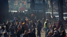Crowd Of People Deep In City Bokeh. Lots of people walking near city road with vehicles moving in the background - Useful generic scene that resembles many major stock video
