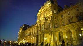 Crowd of people enjoying night view of Louvre Palace, sightseeing tour to Paris stock footage
