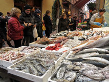 Crowd of people in front of a stand of fresh fish at the market outdoor Stock Image