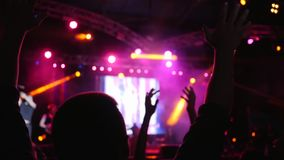 Crowd of people with hands up on background stage illuminated by floodlights at concert stock footage