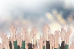 Crowd of people and hands up. With a blurred background Stock Photos