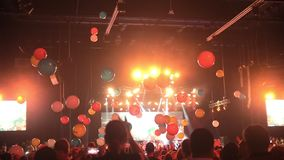 Crowd of people having fun at a concert with balloons flying around the concert hall stock footage