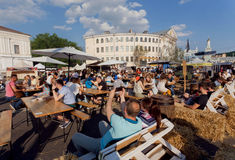 Crowd of people having lunch at sunny outdoor foodcourt under blue sky, during big city weekend Royalty Free Stock Images