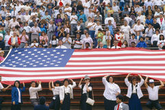 Crowd of people holding up American flag Royalty Free Stock Photos