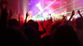 Crowd of people illuminated by colorful light during a concert stock footage
