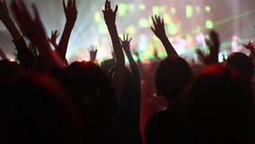 Crowd of people illuminated by colorful light during a concert stock video footage