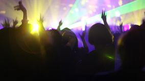 Crowd of people illuminated by colorful light during a concert stock video