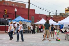 Crowd of people including boy on skateboard and child with bubbles in front of tents at Blue Dome street fair in Tulsa Oklahoma US royalty free stock images