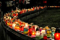 Crowd of people lighting candles in city center, mourning victim. S in terrorism attacks and revolutions, sadness moment Stock Photo