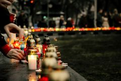 Crowd of people lighting candles in city center, mourning victim. S in terrorism attacks and revolutions, sadness moment Royalty Free Stock Photo