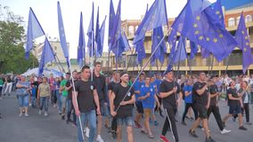 Crowd of people with lots of EU flags are walking along city street. KHERSON, UKRAINE - MAY 20, 2019: Festival Melpomene of Tavria, crowd of people with lots of stock footage
