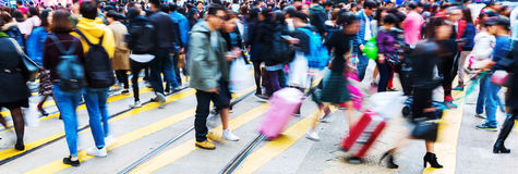 Crowd of people in motion blur crossing a street Stock Image