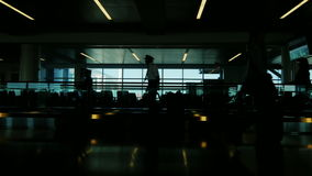 A crowd of people moved by a large JFK airport terminal in New York. Silhouettes without recognizable faces stock video