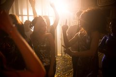 Crowd of People in Nightclub. Crowd of trendy young people dancing in nightclub and enjoying party, focus on beautiful women wearing glittering tops on dance Royalty Free Stock Images