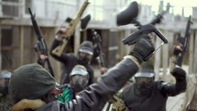 Crowd people in paintball mask lift up close up weapon, begin fanatic 4K strike.