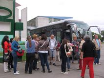 A crowd of people standing near the passengers of the tour bus arrived tourists stop royalty free stock images
