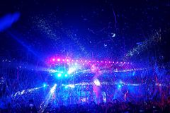 Crowd of people at a pop rock music concert. Crowd of people being showered in streamers and confetti at a pop rock gig. Blue and pink lights shine out from the Royalty Free Stock Image