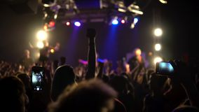 A crowd of people at a music concert raised their hands. A laughing crowd in front of bright colorful stage lights stock video