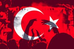 Turkey flag, crowd of people. Crowd of people with raised arms over blending Turkey flag royalty free stock image