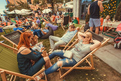 Crowd of people relaxing in loungers with drinks during popular outdoor Street Food Festival Royalty Free Stock Photos
