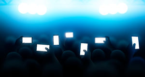 A crowd of people shooting a concert on the phones. Vector illustration. People with phones at the concert. Realistic illustration with the crowd Stock Illustration