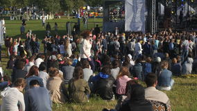 Crowd of people sitting on the grass watching. Crowd of people sitting on grass watching concert stock footage