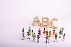 A crowd of people is standing and looking at the letters of the alphabet ABC. Available education, kindergartens and schools, royalty free stock photo