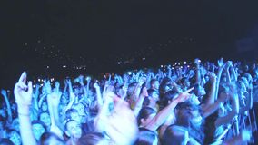 Crowd of people sway hands on live rock concert in nightclub. Spotlights. Illumination stock video footage