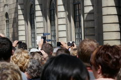 Crowd of people taking photographs. Crowd of people standing outside a building in the sunshine taking photographs on camera and mobile devices viewed from Stock Photography