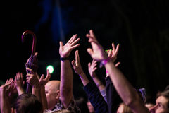 Crowd of people with their hands up during the rock concert on dark background royalty free stock image
