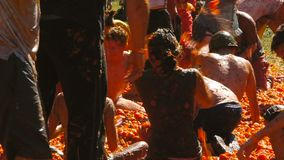 A battle of tomatoes, People are throwing tomatoes. A crowd of people throws crushed tomatoes into each other, a battle of tomatoes, tomato festival stock video