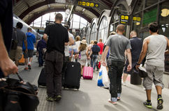 Crowd of people at a train station. A crowd of people at a modern train station in Sweden. People with luggage are walking along the building royalty free stock photo